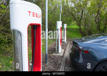 Tesla car next to supercharger at service area in UK - Stock Photo
