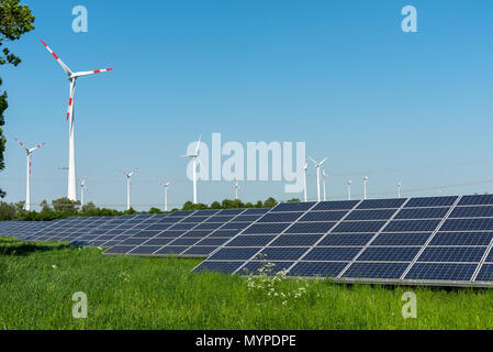 Wind engines and solar panels on a sunny day seen in Germany - Stock Photo