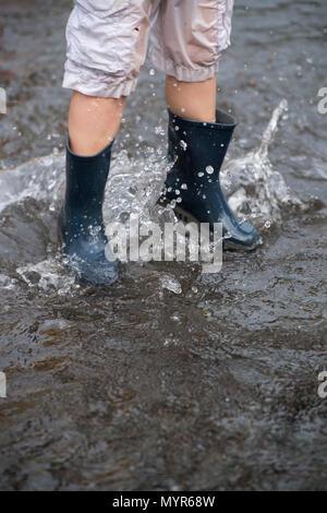 Boys wearing wellingtons splashing in flood water in a street after torrential rain - Stock Photo