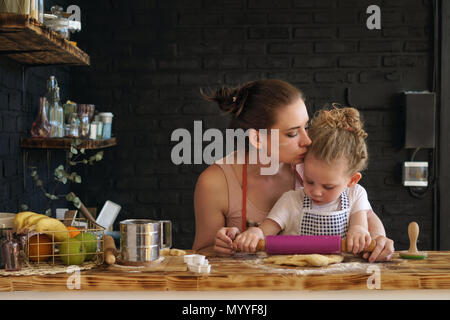 Young mother and daughter prepare cookies in kitchen. They are in aprons. Little girl rolls dough with rolling pin. Mother kisses child, encouraging - Stock Photo