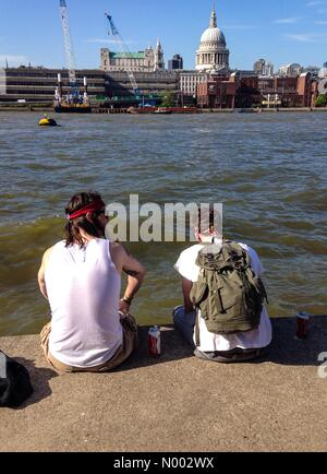 London, UK. 21st May, 2015. Two men enjoy the afternoon sunshine  on the banks of the Thames. Credit:  Paul Swinney/StockimoNews/Alamy - Stock Photo