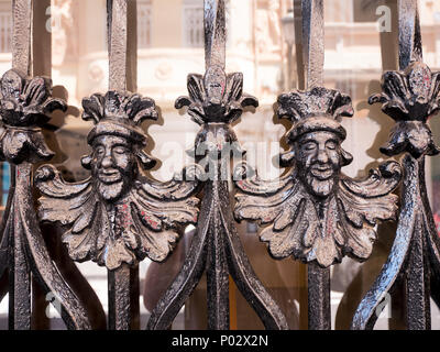 artistic gate made of wrought iron depicting two heads of kings in Valencia, spain - Stock Photo