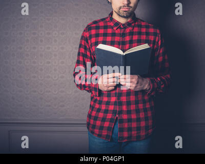 A young man wearing a red flannel shirt is reading a book in a luxury living room - Stock Photo