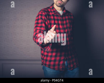 A young man wearing a red flannel shirt is pointing - Stock Photo