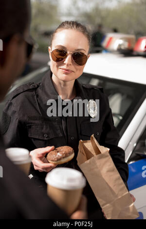 close-up shot of police officers with paper cups of coffee and doughnut - Stock Photo