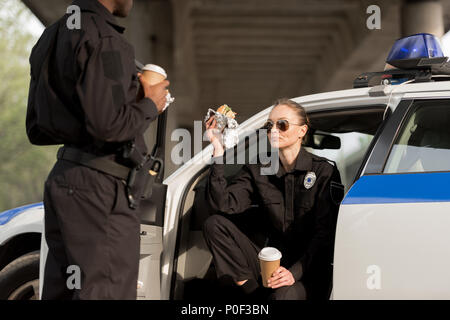 two police officers drinking coffee and eating burger - Stock Photo