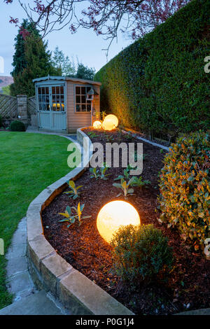 Corner of beautiful, landscaped, private garden with contemporary design, border plants, summerhouse & globe lights at dusk - Yorkshire, England, UK. - Stock Photo