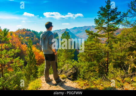 Young man in looking on the colorful autumn mountains in Sulov, Slovakia - Stock Photo