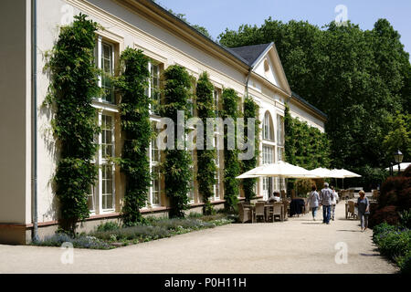 Bad Homburg, Germany - May 19, 2018: Visitors sitting under umbrellas at garden tables at the Orangery in the spa gardens on May 19, 2018 in Bad Hombu - Stock Photo