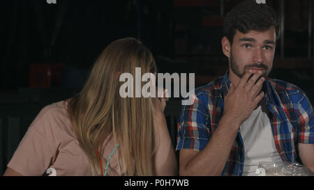 Scared girl closing her eyes with her hands watching scary movie in the cinema - Stock Photo