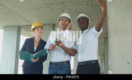 Executive team on construction site discussing project, using smartpone and digital tablet - Stock Photo