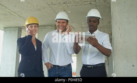Executive team on construction site discussing project, using tablet, having phone calls with smartphone - Stock Photo