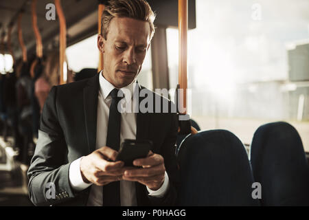 Focused young businessman wearing a suit standing on a bus during his morning commute reading text messages - Stock Photo