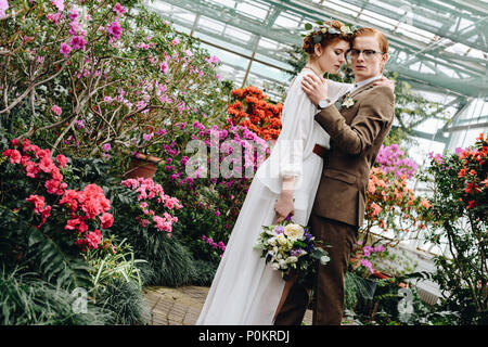 beautiful tender young wedding couple with bouquet standing between flowers in botanical garden - Stock Photo