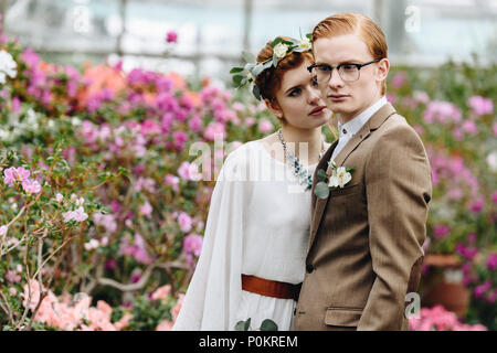 stylish young elegant wedding couple standing together between flowers in botanical garden - Stock Photo