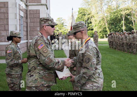 U.S. Army Lt. Col. Shawn J. Shutts, deputy commander of the 369th Sustainment Brigade, New York Army National Guard, is presented the Shield of Saint Christopher by Col. Stephen Bousquet, commander of the 369th Sustainment Brigade, during a ceremony at Camp Smith, N.Y., June 2, 2018. The Military Order of Saint Christopher recognizes those individuals who have made significant contributions to the U.S. Army Transportation Corps. (U.S. Army National Guard photo by Sgt. Jeremy Bratt) - Stock Photo