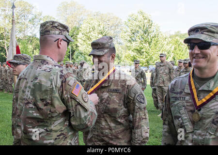 U.S. Army Maj. Navin Kalicharan, operations officer of the 369th Sustainment Brigade, New York Army National Guard, is presented the Shield of Saint Christopher by Col. Stephen Bousquet, commander of the 369th Sustainment Brigade, during a ceremony at Camp Smith, N.Y., June 2, 2018. The Military Order of Saint Christopher recognizes those individuals who have made significant contributions to the U.S. Army Transportation Corps. (U.S. Army National Guard photo by Sgt. Jeremy Bratt) - Stock Photo