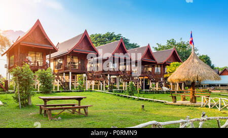 Village and bungalows along Nam Song River in Vang Vieng, Laos. - Stock Photo