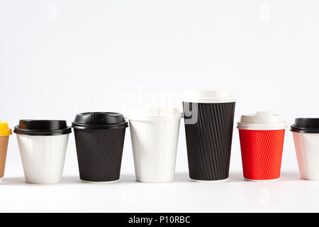 Endless row of disposable coffe cups of different colors and sizes on white background with copy space - Stock Photo