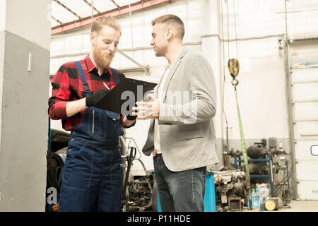 Car Technician Talking To Client - Stock Photo