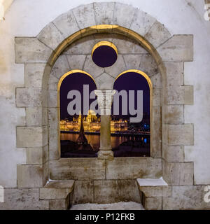 The Hungarian Parliament building seen through the windows of Fisherman's Bastion in Budapest in winter - Stock Photo