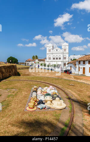 Hats laid out displayed for sale to tourists on the Galle Fort ramparts by the iconic white Meeran Jumma Mosque, Galle, Southern Province, Sri Lanka - Stock Photo