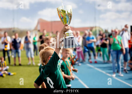 Young Boy Raising Golden Football Cup. Winning Youth Football Team Celebrating Success. Kids School Football Tournament Handing Out Prizes - Stock Photo