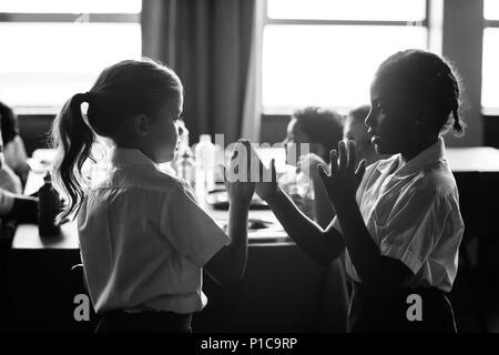 Girls playing clapping game - Stock Photo
