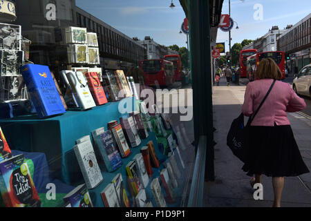 People walk past an independent bookshop on Kentish Town Road. Shops are closing down and the high street is in decline as people move to do their sho - Stock Photo