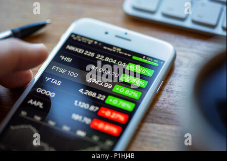 BATH, UK - JUNE 11, 2018 : An Apple iPhone 6 on a desk displaying stock market information using the Apple Stock app. A human hand hovers above the FT - Stock Photo