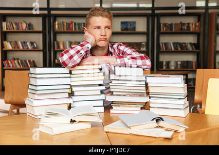 Bored teenage boy sitting at the library table with big stacks of books - Stock Photo