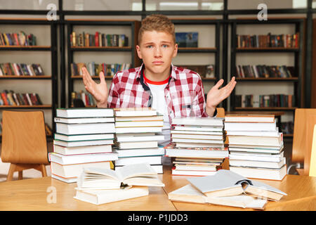 Confused teenage boy sitting at the library table with big stacks of books - Stock Photo