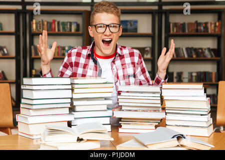Excited teenage boy sitting at the library table with big stacks of books - Stock Photo