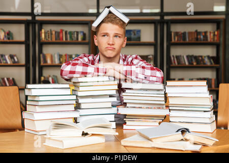 Upset teenage boy sitting at the library table with big stacks of books - Stock Photo