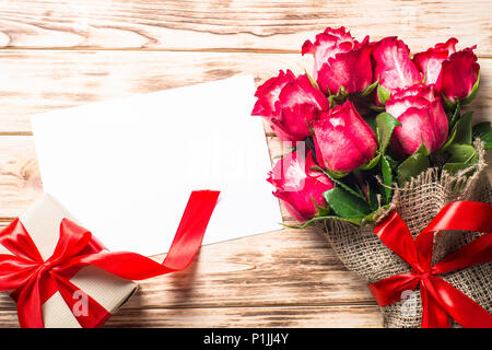 Red rose flower on wooden table and paper sheet. Top view with copy space. Flower background. - Stock Photo