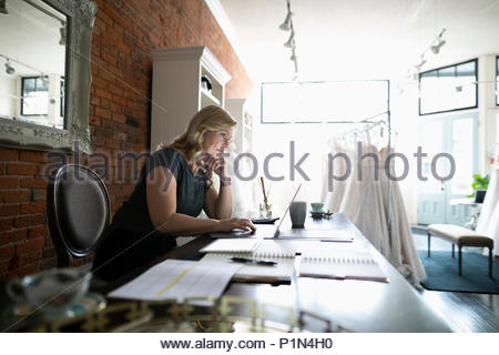 Bridal boutique owner working at laptop - Stock Photo