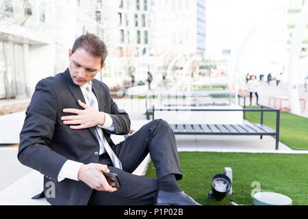 Young businessman cleaning dusting off suit sitting on bench in urban green park looking down with tie on interview break - Stock Photo
