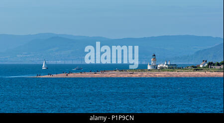 CHANONRY POINT MORAY FIRTH SCOTLAND WITH LIGHTHOUSE PEOPLE ON THE BEACH AND KESSOCK BRIDGE INVERNESS IN DISTANCE - Stock Photo