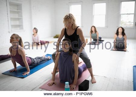 Yoga instructor helping woman practicing upward facing dog pose in yoga class - Stock Photo