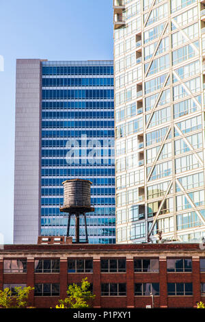 Buildings in downtown Chicago with a water reservoir on the rooftop of a residential building, showing the contrast of old and new buildings - Stock Photo