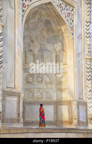 Woman standing outside Taj Mahal in Agra, Uttar Pradesh, India. Taj Mahal was designated as a UNESCO World Heritage Site in 1983. - Stock Photo
