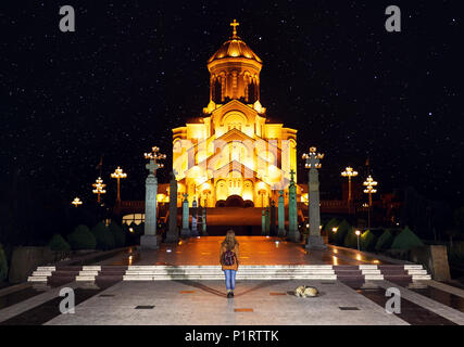 Woman near The Holy Trinity Cathedral or Tsminda Sameba Church at night in Tbilisi, Georgia - Stock Photo