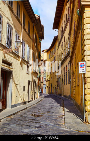 Perspective view of narrow cobblestoned street between colorful stone old buildings in sunlight, Florence, Italy - Stock Photo