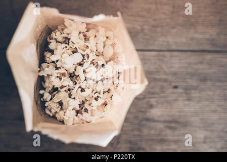 top view of fresh popcorn in brown paper bag on rustic wooden table - Stock Photo