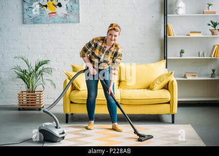 beautiful woman cleaning carpet with vacuum cleaner at home - Stock Photo