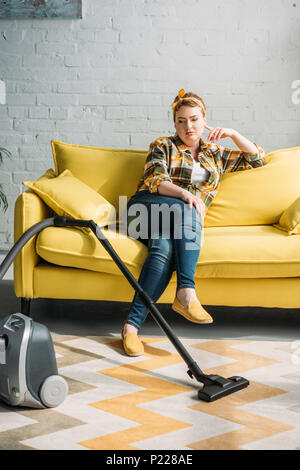 beautiful woman sitting on sofa and looking at vacuum cleaner at home - Stock Photo