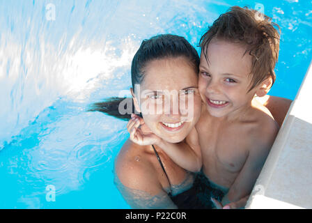 happy smiling caucasian family consisting of mother and child embracing in swimming pool - Stock Photo