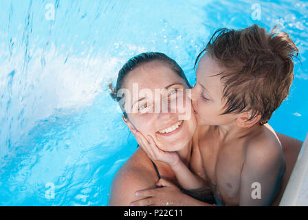 cute little caucasian kid kissing his happy smiling mother in summer azure pool in resort - Stock Photo