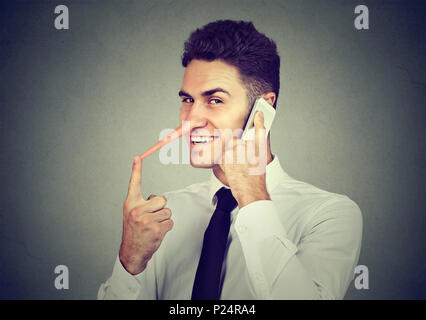 Sly young man with long nose talking on mobile phone isolated on gray wall background. Liar concept. Human emotion feelings, character traits - Stock Photo
