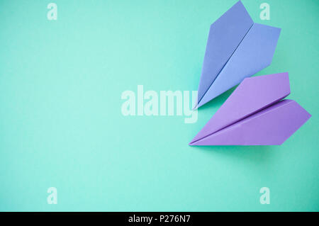 Flat lay of two purple paper planes on pastel pink and blue background with text space. - Stock Photo